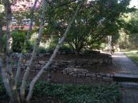 Garden landscape design - natural-looking stone retaining walls around flower beds