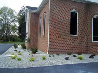 Landscape design for church flowerbed, shrubs with gray stones