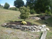 Flower bed on hill with rock retaining wall around the bottom side