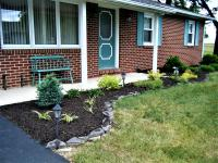 Rock landscape border around bark mulch shrubbery bed