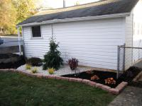 Back yard ideas - Red brick flower bed border with part stone and part mulch ground cover around the plants