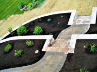 Paver sidewalk through mulched flower beds with retaining wall