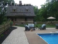 Mulched flower bed and cobblestone walkway around swimming pool
