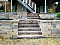 Block retaining wall and steps built with blocks of various colors and sizes
