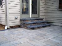 Outdoor stone steps and patio laid with large block pavers