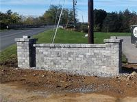 Concrete brick wall with columns on each end built at the end of the driveway