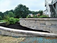Curved retaining wall built with blocks of different colors and sizes to give a natural look