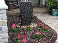 Modern-look water fountain set in flower bed beside stamped concrete sidewalk