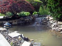 Waterscaping with large and small rocks around waterfalls running into a pond
